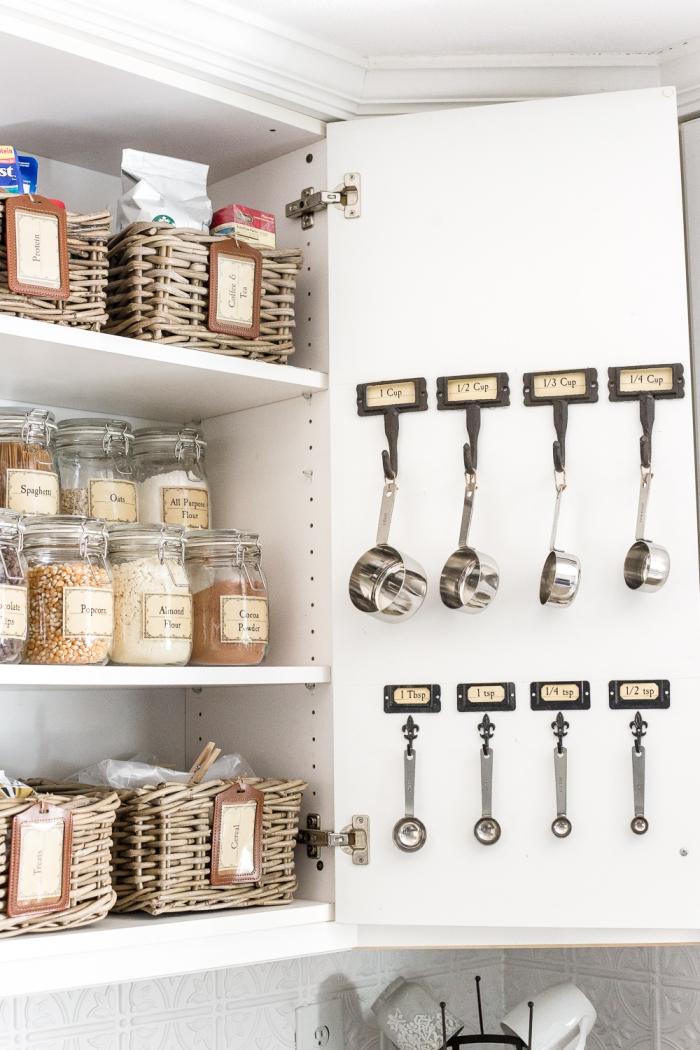 des crochets avec petites étiquettes posés sur la porte du placard pour y suspendre des cuillères doseuses, des solutions d'amenagement placard cuisine avec des paniers et des bocaux à aliments