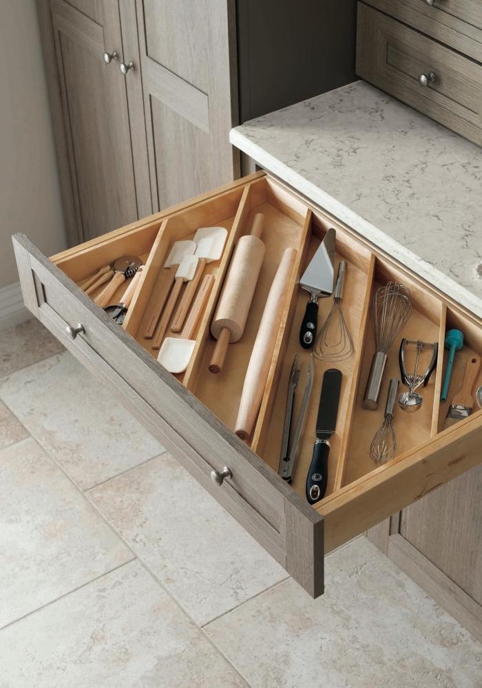 organisateur placard cuisine pour mieux ranger les couverts, un tiroir compartimenté à la verticale, avec un intérieur en bois clair