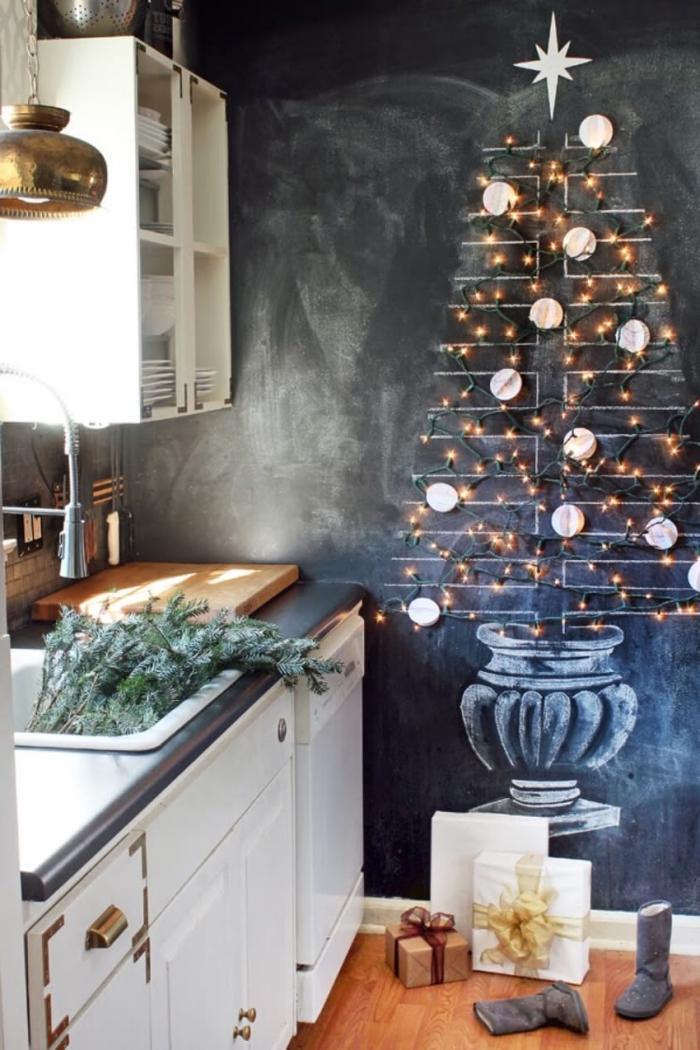 dessin à la craie d'un sapin original sur le mur en ardoise de la cuisine, décoré avec une guirlande lumineuse et des boules en papier
