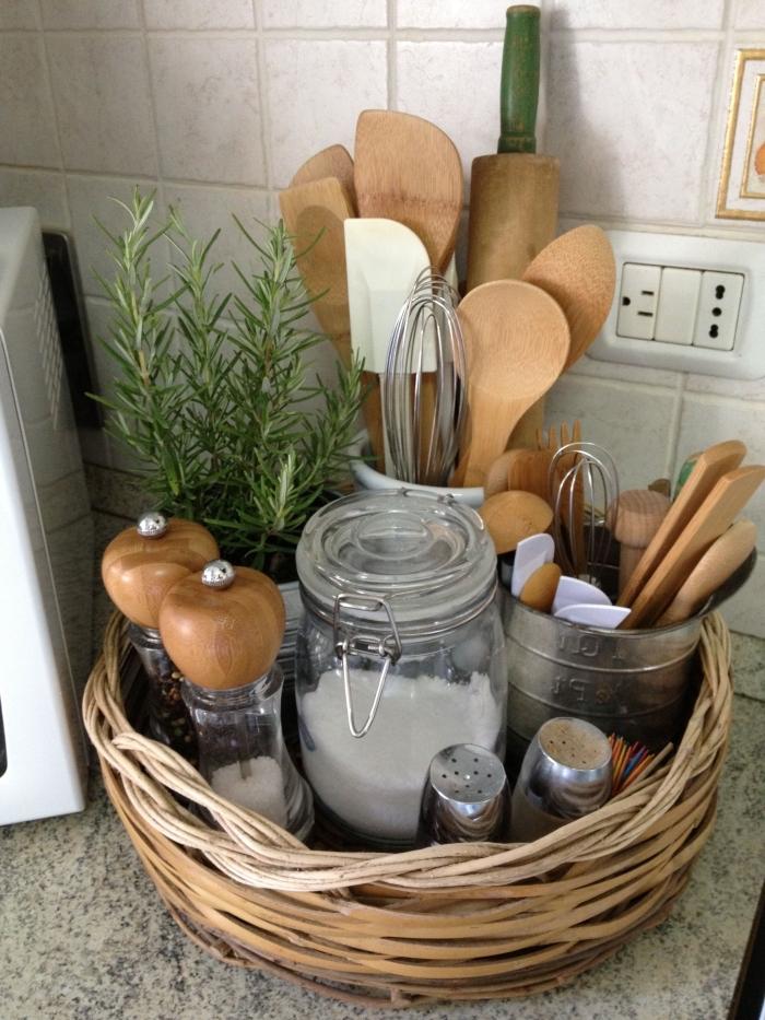 un simple panier de rangement en fibres naturelles qui accueille les ustensiles de cuisine et les pots à épices les plus utilisés, un simple astuce rangement cuisine qui permet de dégager les tiroirs et le plan de travail