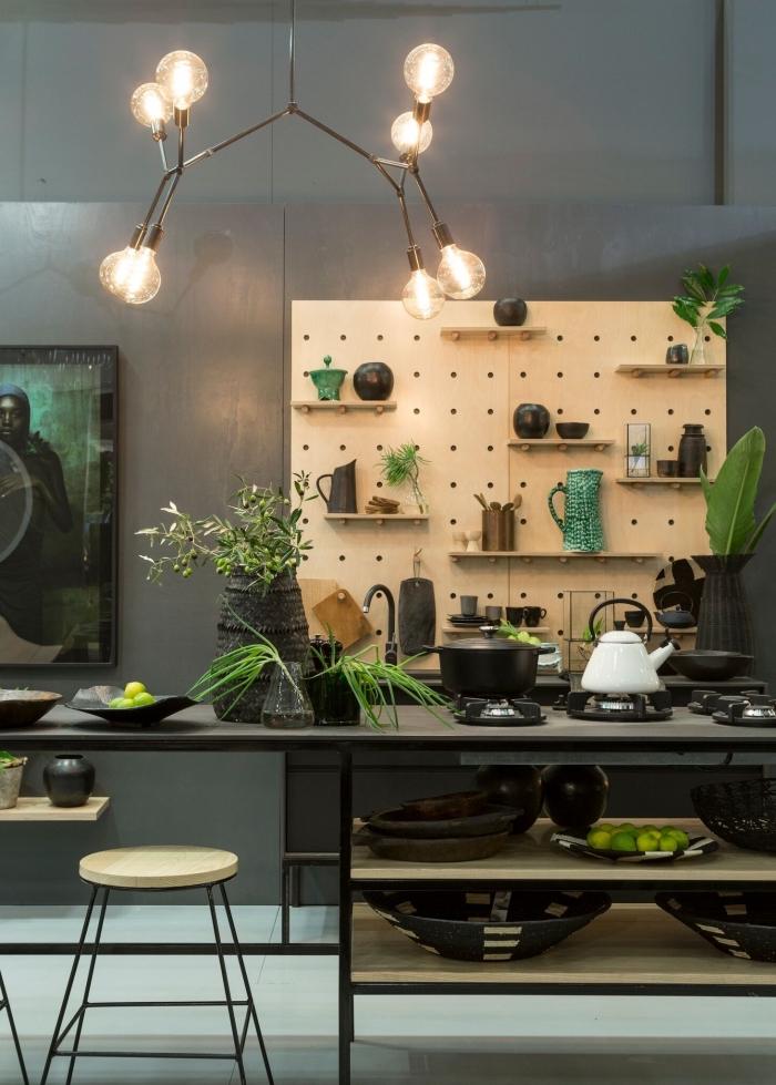 une cuisine moderne noir et bois équipée d'un îlot central de style minimaliste en acier noir, avec un un rangement mural fonctionnel en tableau perforé