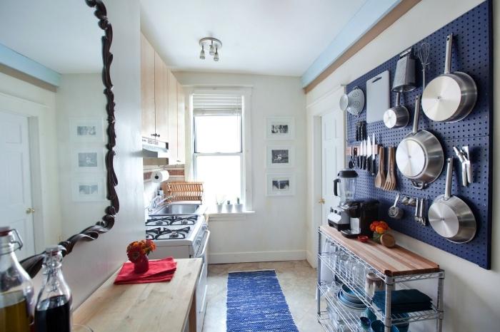 panneau perforé d'accrochage pour ranger la vaisselle et les ustensiles de cuisine disposé au-dessus d'une étagère en bois et métal, idée de rangement fonctionnel et gain de place pour aménager une petite cuisine optimisée
