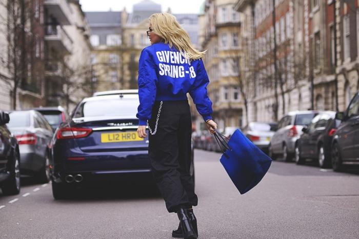 tenue swag fille, bottes noires, veste de sport script au dos, cheveux blonds, tenue décontractée