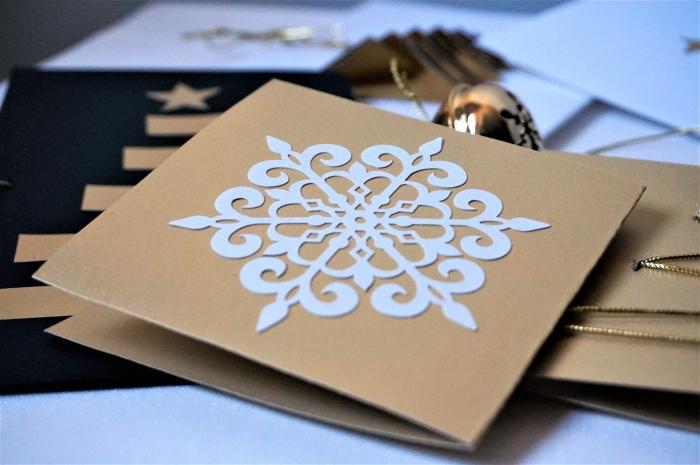 jolie carte noel à réaliser avec papier kraft brun, modèle de flocons de neige à découpé de papier cartonné blanc