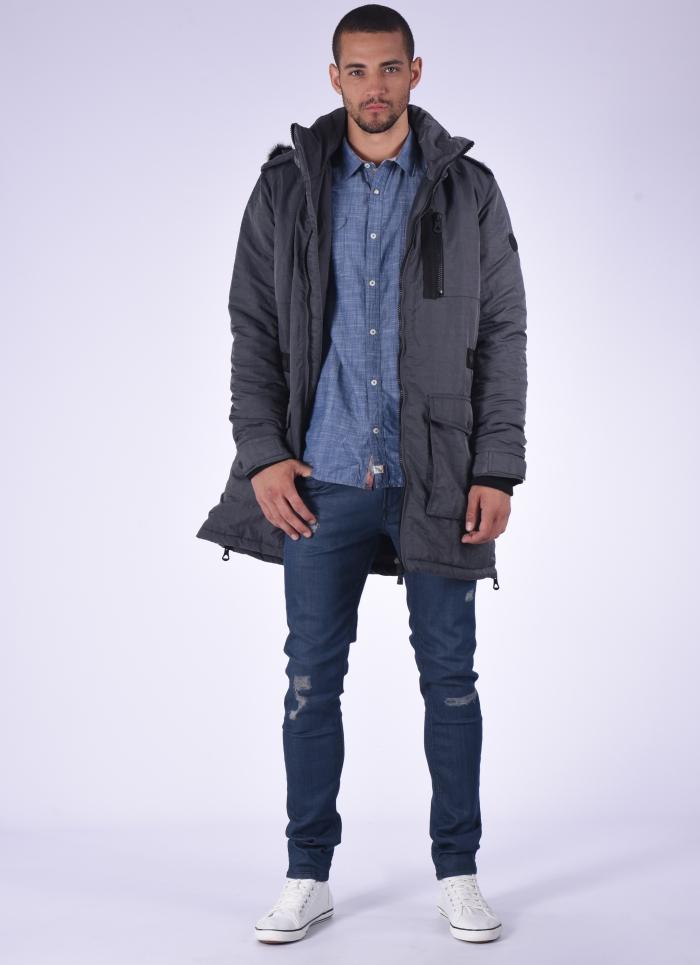 look homme urbain chic avec un modèle de parka technique chaud couleur gris avec grandes poches et capuche amovible, porté de façon casual chic avec un jean slim et une chemise imitation denim