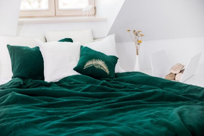 ambiance cozy dans une chambre sous combles, idée peinture murale tendance, déco de chambre blanche avec accessoires en vert foncé