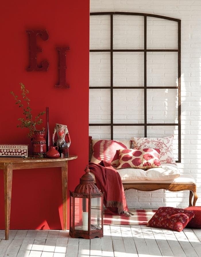 deco chambre femme aux murs rouges, design intérieur de style ethnique chic avec objets en bois, coin cozy avec coussins et tapis en blanc et rouge