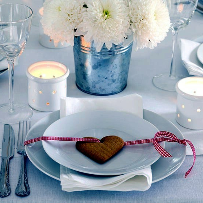 petit biscuit en forme de coeur avec ruban  carr s mis sur assiette blanche sceau m tallique comme vase bougeoirs blancs verres