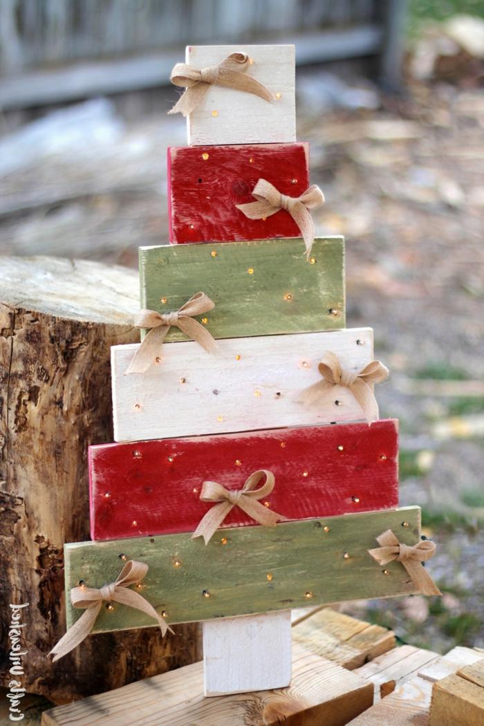 sapin en palette de bois, morceaux de planches peints en couleurs festives, tronc, rubans de jute