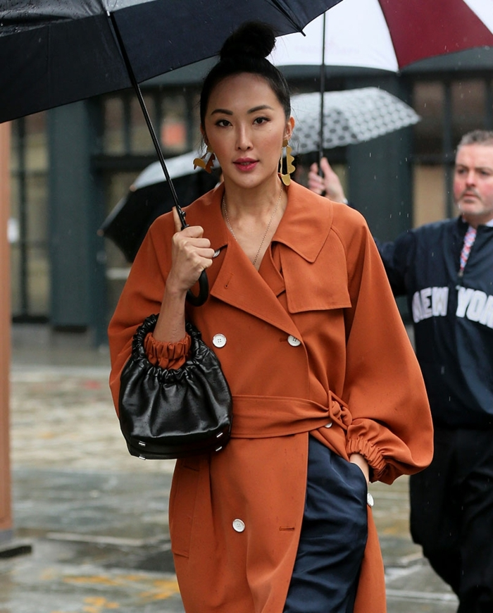manteau femme couleur terracotta, sac noir poignée ronde, pantalon bleu élégant, manteau boutons blancs