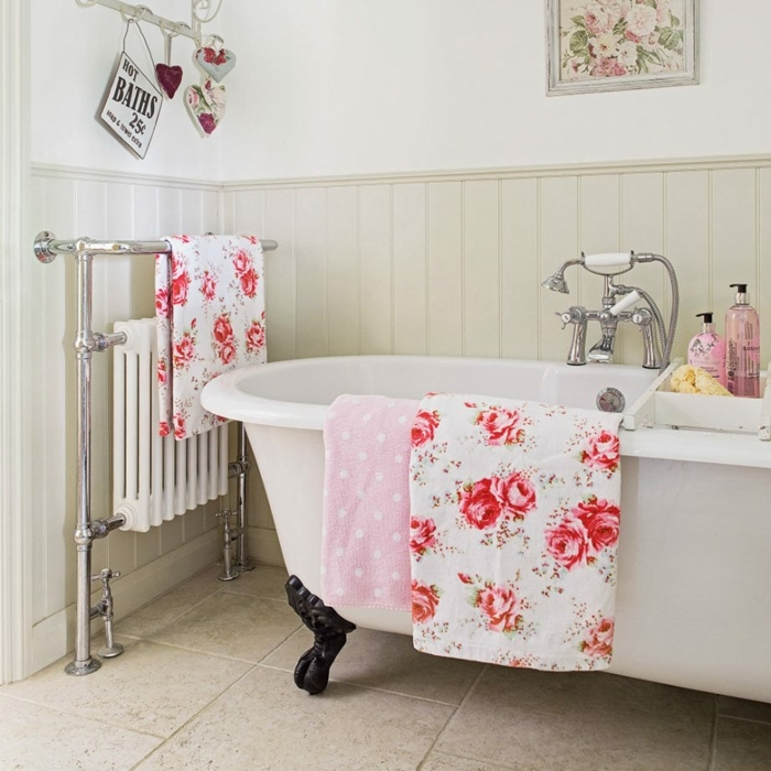 baignoire blanche aux pieds noirs, tissus motifs floraux, serviette rose, robinet vintage, lambris mural, radiateur avec porte serviette, peinture fleurs roses, déco d'espace shabby