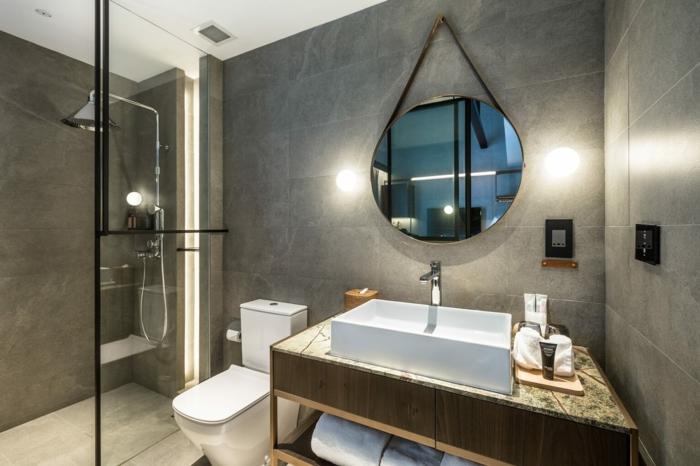 cloison en verre au profilé noir, meuble sous vasque avec rangement ouvert, miroir rond accroché, douche au ras du sol