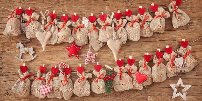 sachets de jute suspendus à des pinces à linge avec décoration de coeurs rouges sur fil et chiffres en bois, calendrier de l avent rustique chic
