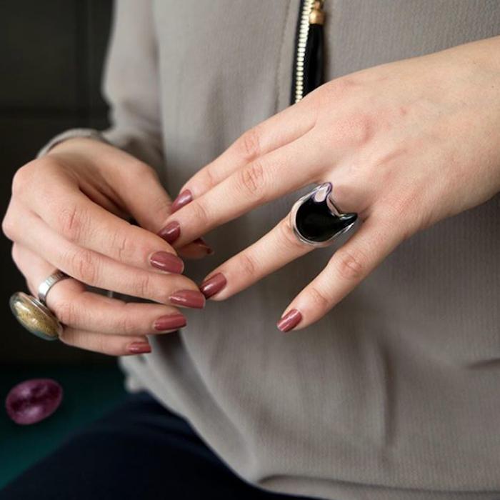 photo de main de femme avec bagues originales en verre avec intérieur liquide et perles pour une idée cadeau de bijoux originaux