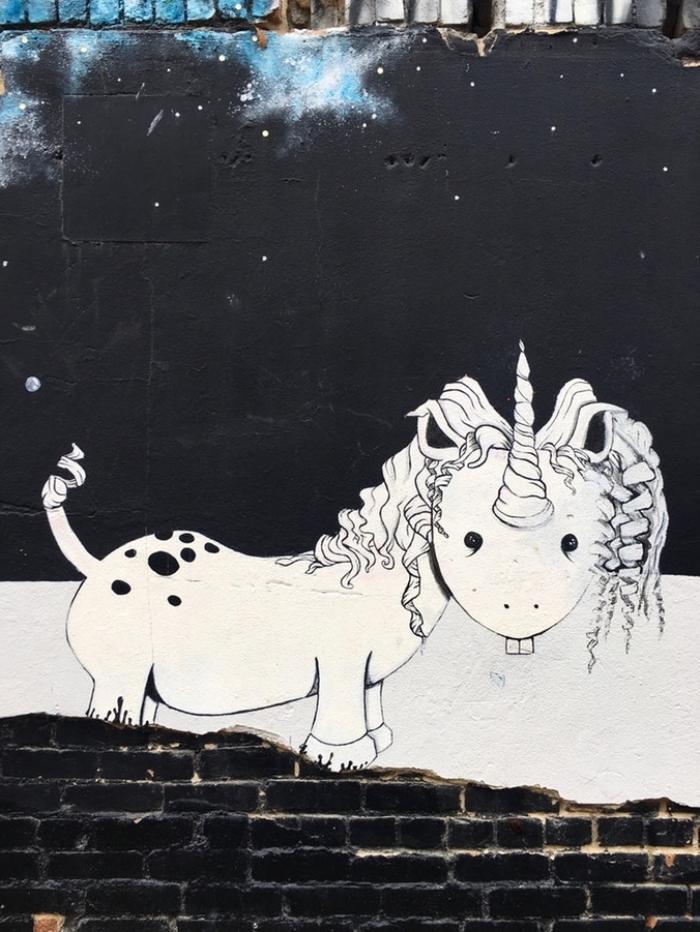 photo licorne d'un grafiti avec un drôle de licorne insolite aux pattes courtes avec deux dents réalisé sur un mur de briques noir