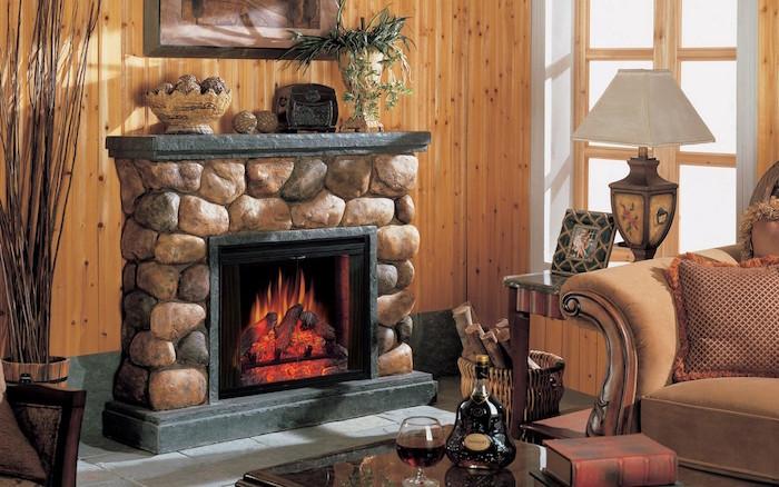 fausse cheminée en fausses pierres avec faux feu electrique ecran dans salon avec décoration type chalet avec mur en bois et meubles anciens