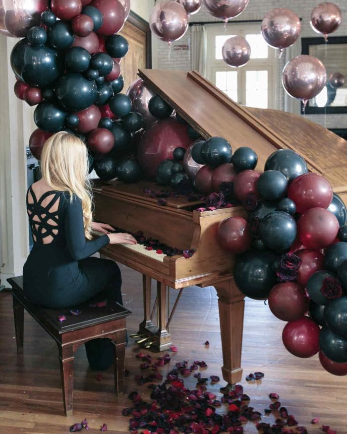 piano en bois, banquette en bois, guirlande de ballons foncés, ballons mauves suspendus en l'air