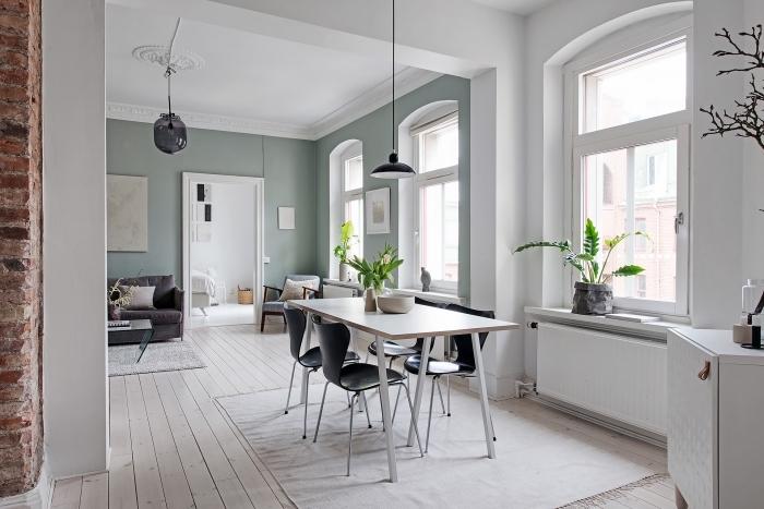 déco scandinave dans un appartement au plafond blanc et murs verdâtres, peinture salle a manger vert pastel