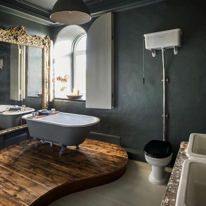 plateforme en bois, murs gris, grand plateau de lavabo en ciment, grand miroir cadre doré, lampe usine, fenêtre arquée