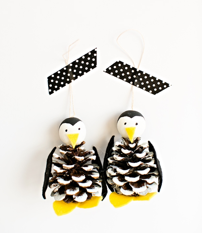 pomme de pin aux bouts colorés de peinture blanche avec tête de pingouin en perle de bois et des pattes jaunes