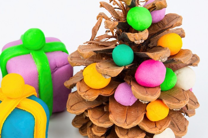 pomme de pin décorée de boules de pate fimo colorées et de petites figurines de cadeaux en pate fimo, deco noel simple a fabriquer