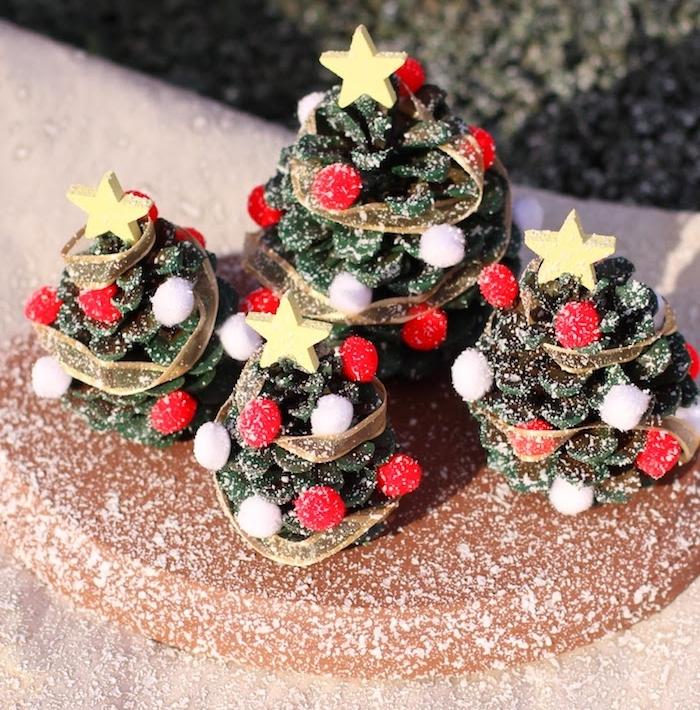 petits sapins de noel en pomme de pin recyclée avec deco de pompon rouge, étoile de bois, neige artificielle saupoudrée