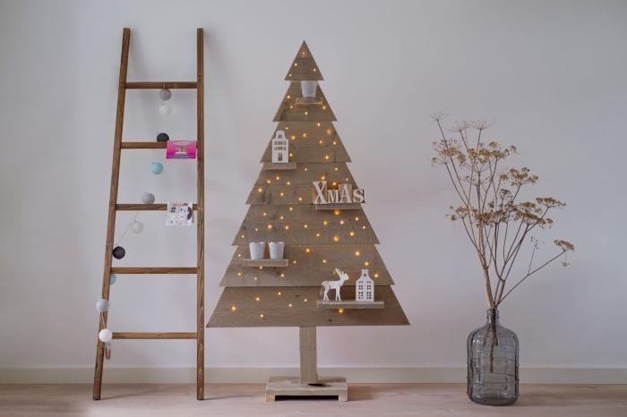décor rustique d'esprit avec un sapin de noel en bois à étagères ornées de motifs de noël, une échelle en bois et un joli vase en verre coloré