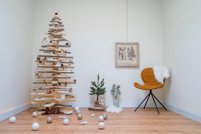 un sapin de noel en bois fabriqué avec des tasseaux de bois, sapin étagère décoré avec des ornements de noël pour une déco naturelle et minimaliste