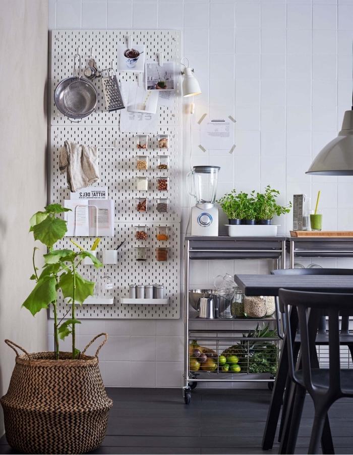 un tableau perforé fixé au mur de la cuisine avec petites étagères, rangement épices et crochets pour suspendre les ustensiles de cuisine, cuisine blanc et noir de style industrielle avec coin repas et une desserte en inox industrielle