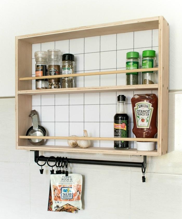 une étagère ouverte à encadrement d'aspect vintage avec une barre à crochets en acier noir qui sert de rangement à épices