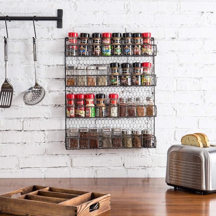 une étagère murale industrielle en fil à quatre niveaux pour ranger des petites boîtes à épices, contrastant avec le mur en briques blanches, un rangement épices mural d'ikea installé au mur à côté d'une abrre porte-ustensiles de cuisine, au-dessus du plan de travail en bois