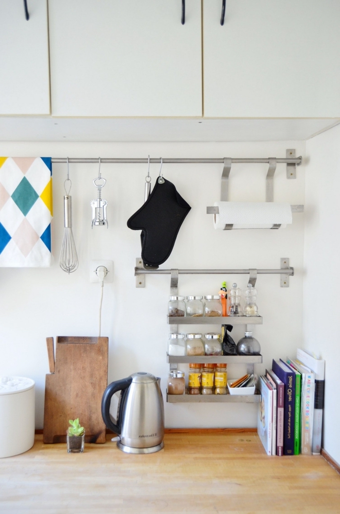 système de rangement mural avec des barres en acier à crochets multiples et un rangement à épices à trois niveaux, installées sur la crédence