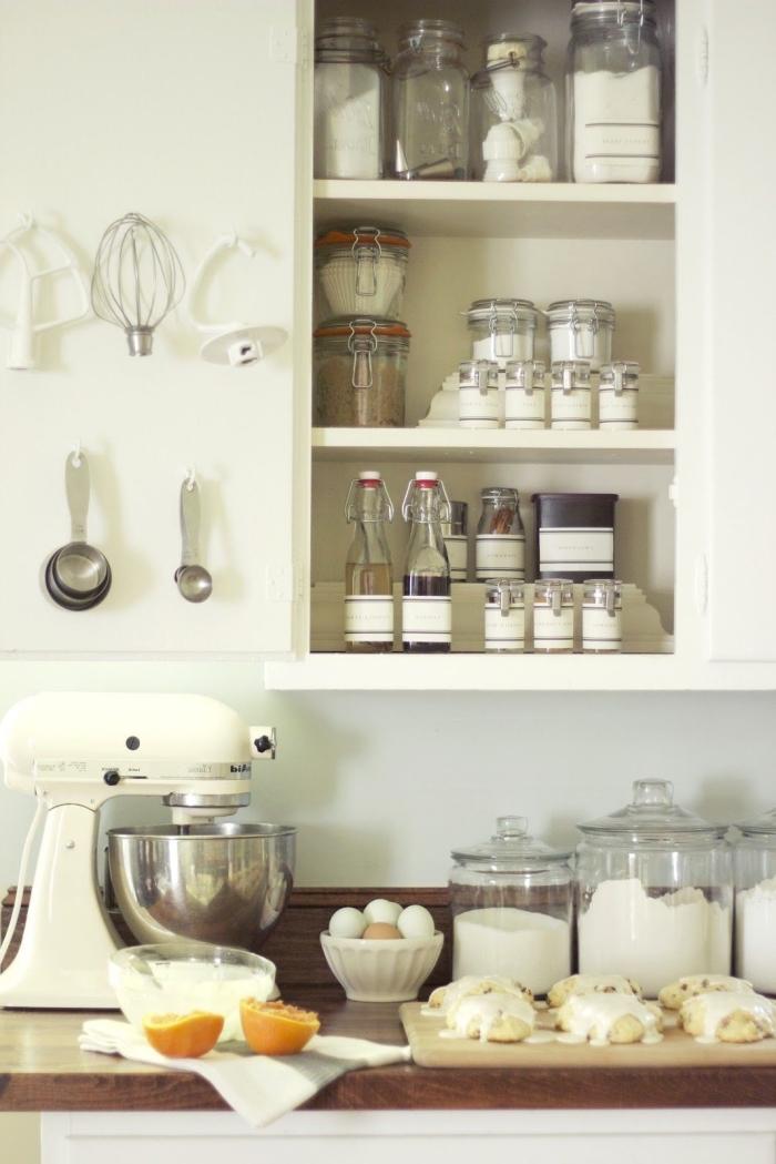 rangement placard cuisine avec des bocaux à couvercles de conservation et de petits crochets à la porte pour les ustensiles de cuisine