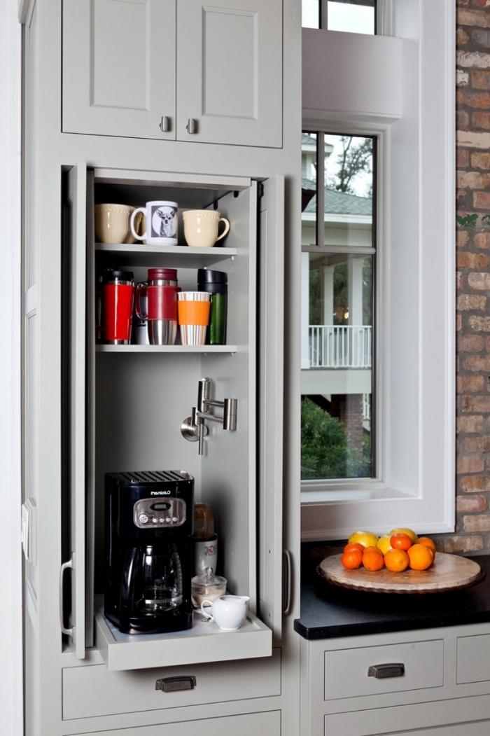 un coin café aménagé dans le placard de cuisine avec des étagères pour les tasses à café et une tablette coulissante pour la machine à café
