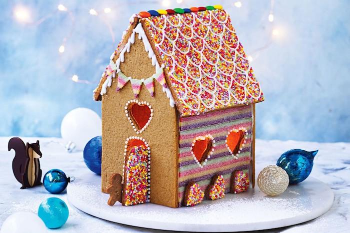 maisonnette gourmande de noel au gingembre avec toiture décorée de vermicelles colorées, mur à rayures colorés et porte vermicelles