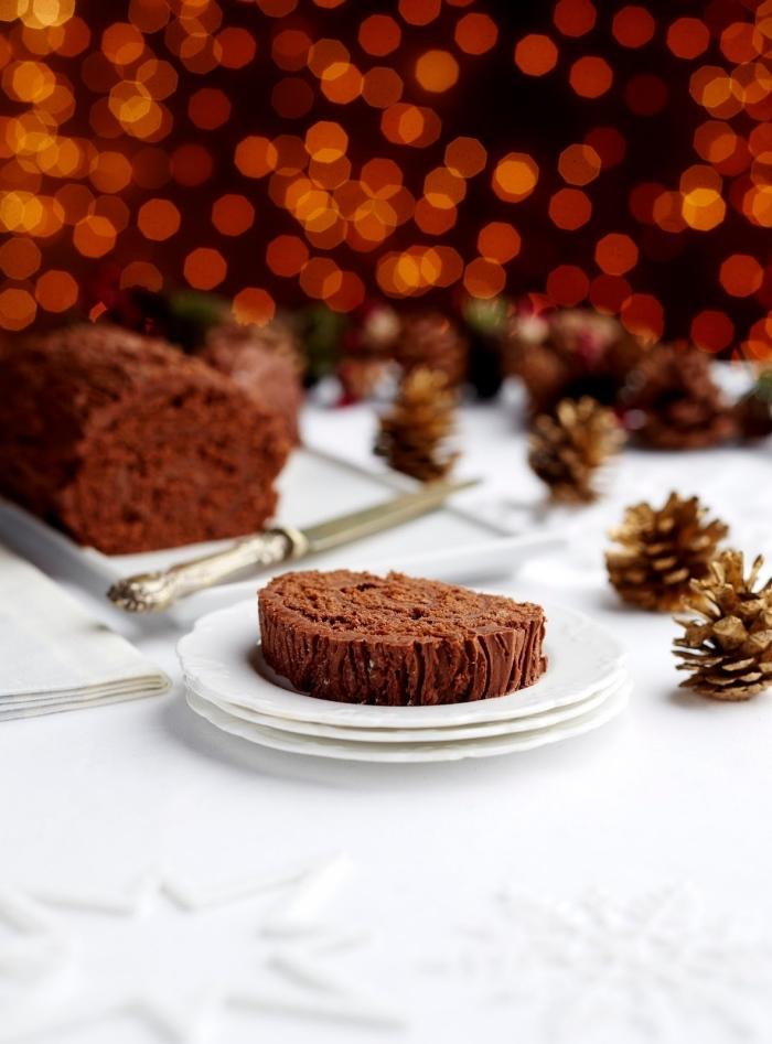 buche de noel maison au chocolat sans lactose et sans gluten, déco de table de noël blanche avec des pommes de pin et des étoiles en papier