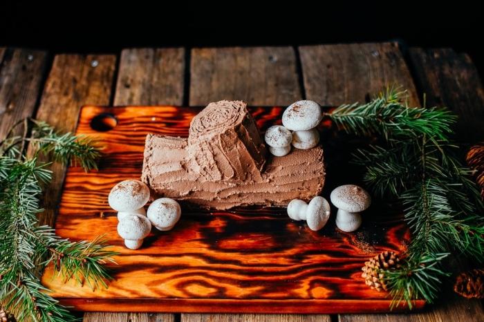 recette buche glacée sans cuisson préparée à base de sablés au chocolat et à la crème chantilly à la noix de coco, décorée avec des champignons en meringue