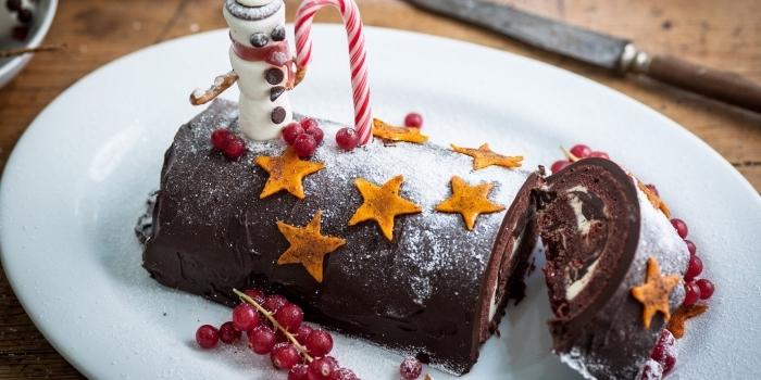 gâteau enroulé de noel façon red velvet cake à la crème au beurre au fromage frais, recette buche patissiere à faire soi-même avec une jolie décoration d'étoiles en courge, de motifs de noel et de la groseille
