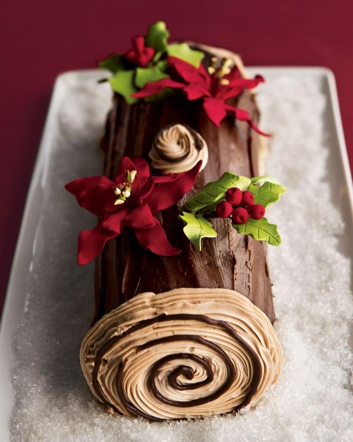 une buche patissiere facile au chocolat, décorée avec des étoiles de noël et des feuilles de houx en pâte à sucre