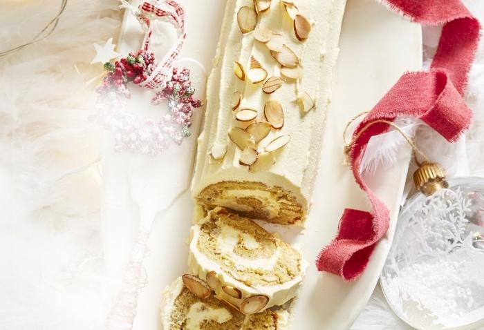 recette de buche de noel classique au chocolat blanc et au gingembre décoré avec des amandes effilées, gâteau roulé au glaçage de chocolat blanc strié