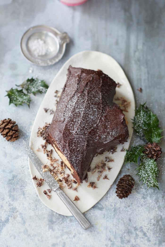 recette de buche de noel traditionnelle au chocolat et caramel au beurre salé dans un joli décor naturel de pommes de pin et de feuilles de houx