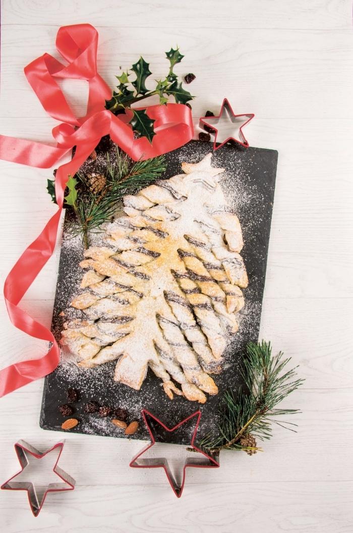 joli sapin de pâte feuilletée au chocolat saupoudré de sucre glace, décoration gâteau de noel facile avec ruban et branches de sapin