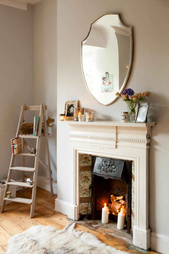 décoration cheminée condamnée avec bougies dans piece cosy scandinave mur gris taupe et sol en bois parquet