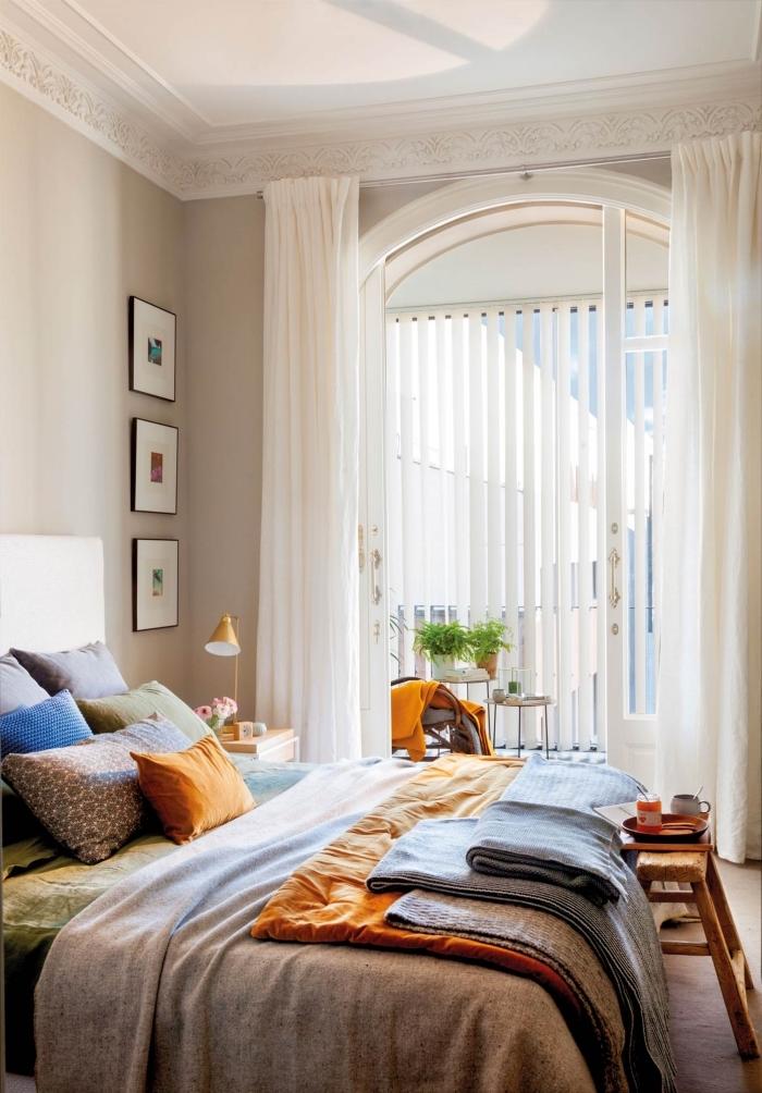 deco chambre femme aux murs en cotton brut, coloris beige doré dans une chambre à coucher avec accessoires en orange