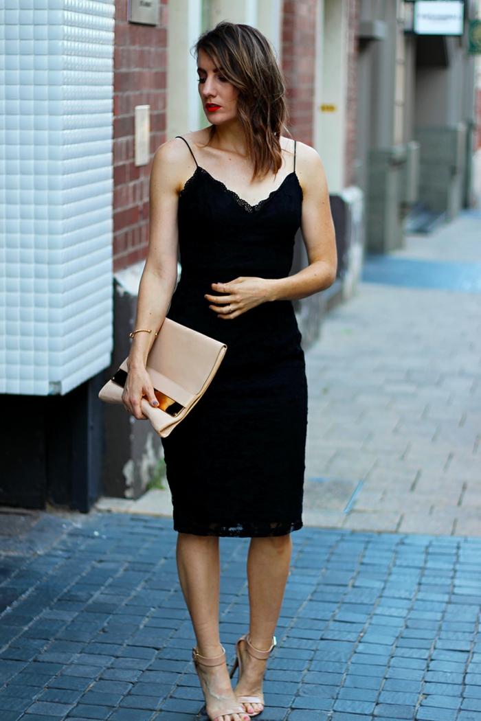 robe noire chic aux fines bretelles, sac enveloppe beige avec motif doré, rouge à lèvre vif, sandales nude