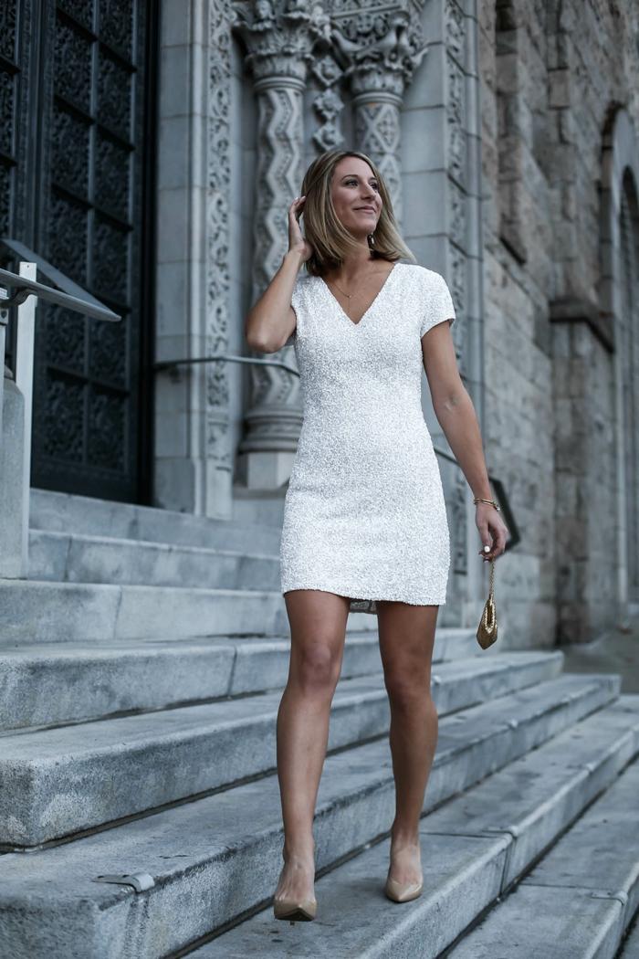 robe blanche, décolleté triangle, clutch doré, chaîne, escarpins nude, jeune femme devant un bâtiment publique