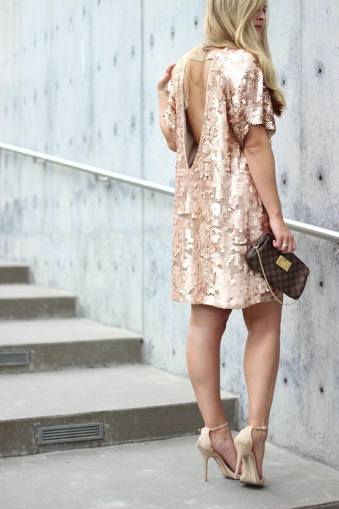 robe rose pailletée mi-longue, sac marron, dos dénudé, cheveux blonds, sandales élégantes