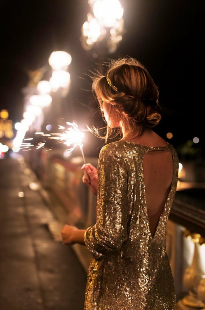 robe glamour dos nu, chignon enroulé, manches longues, jeune femme tenant un feu bengali