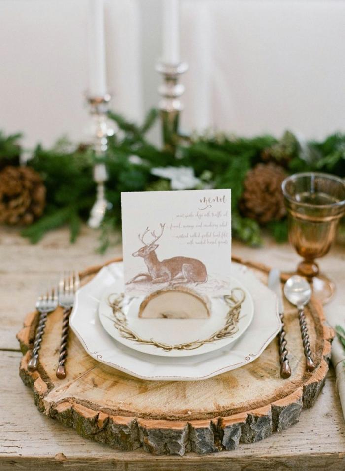 rondin de bois assiette blanche ustensiles vintage carte de papier avec script et dessin de cerf couronne de branches de pins bougeoirs argent s e1541586306275