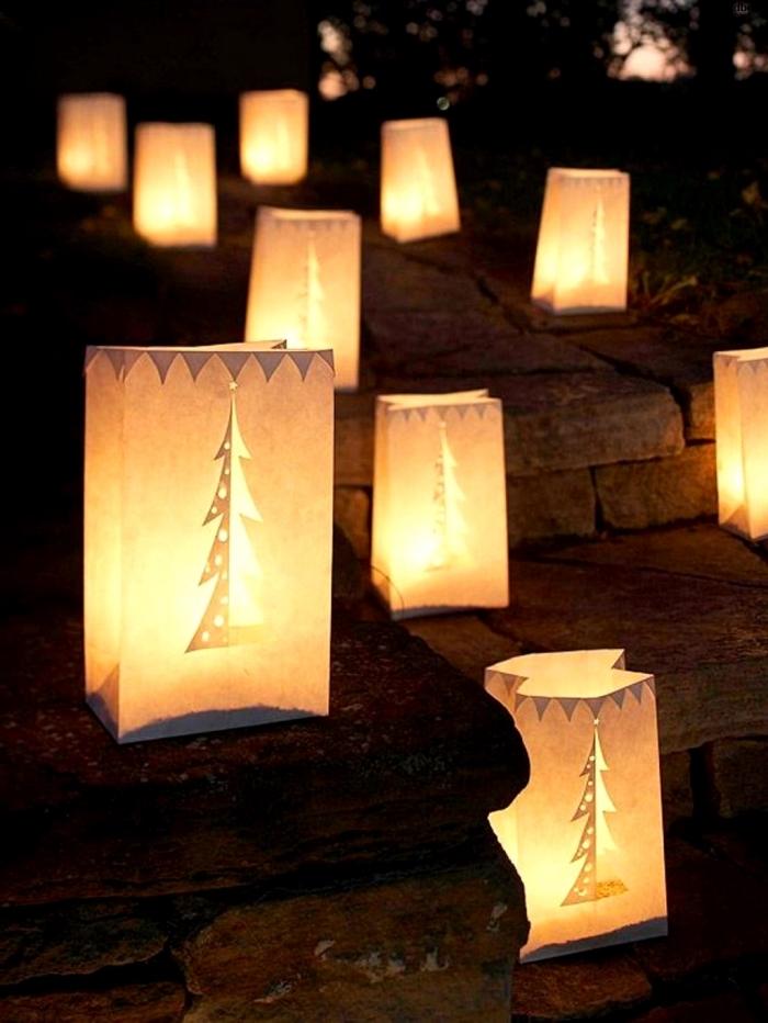 décoration de noël extérieure avec des sacs en papier découpés à bougies led posés au sol en pierre